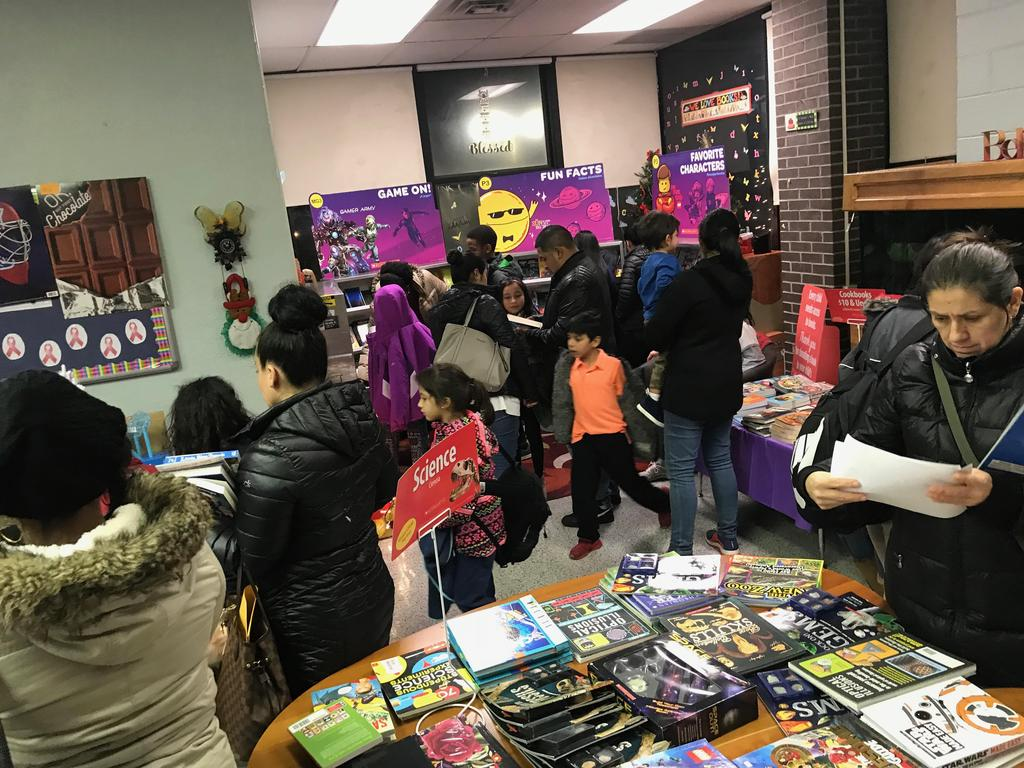 children and parents looking at the book at the book fair