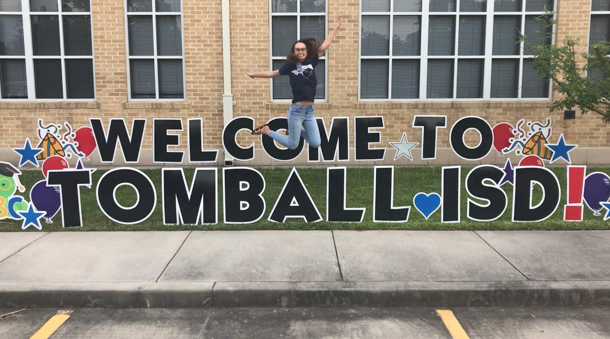 Ms. Cleland is gleefully jumping as high as she can in front of a large yard sign that reads, 'Welcome to Tomball ISD'. She is wearing a navy blue wildcat shirt and is so happy to be working for Tomball ISD.
