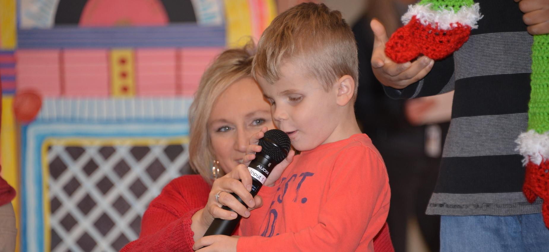 Teacher holding microphone for student