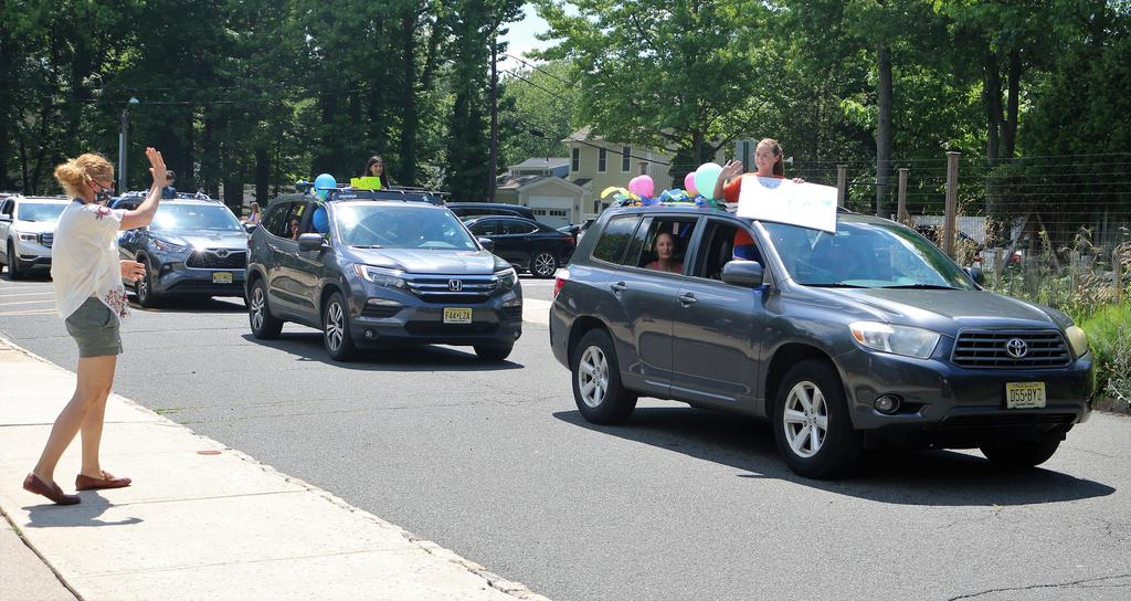 Photo of Tamaques Grade 5 teacher waving at 5th graders passing by in car parade.