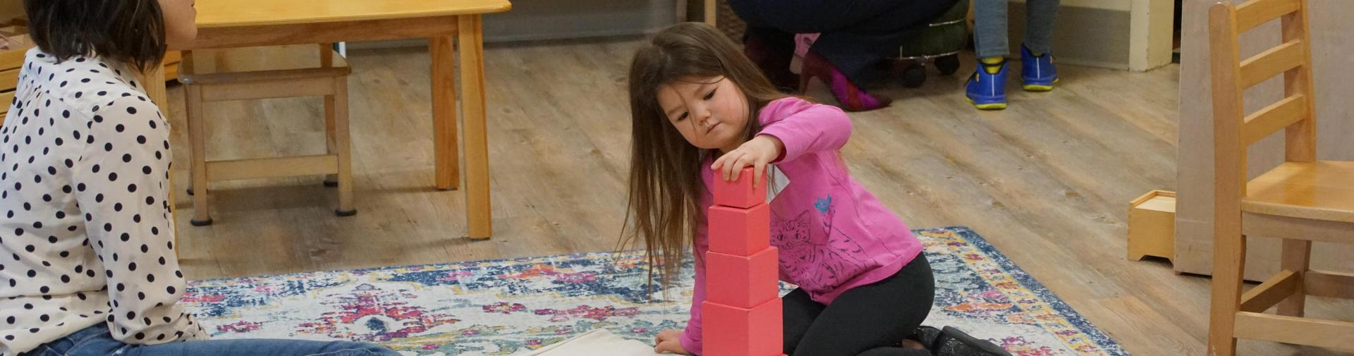 Child building the pink tower