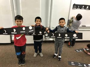 Students holding their moon cycles
