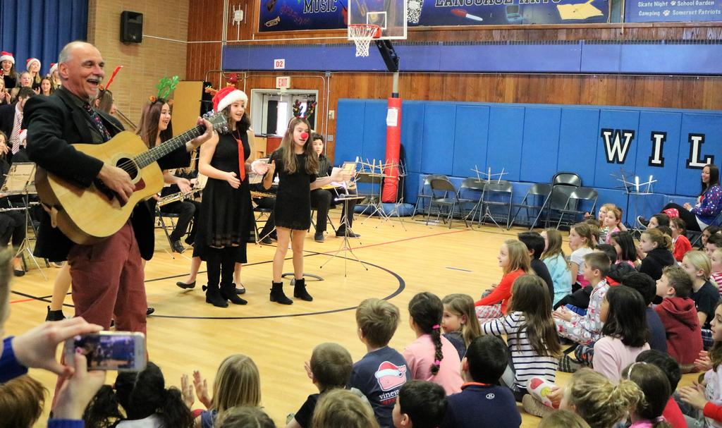 Photo of music instructor Sabino Losco and Roosevelt student musicians performing for Washington School student