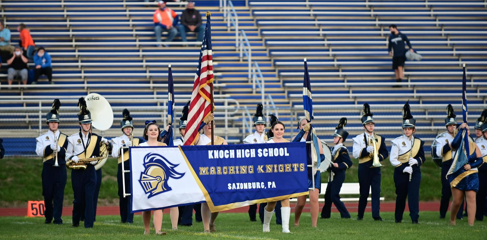 Band members carrying school banner on field