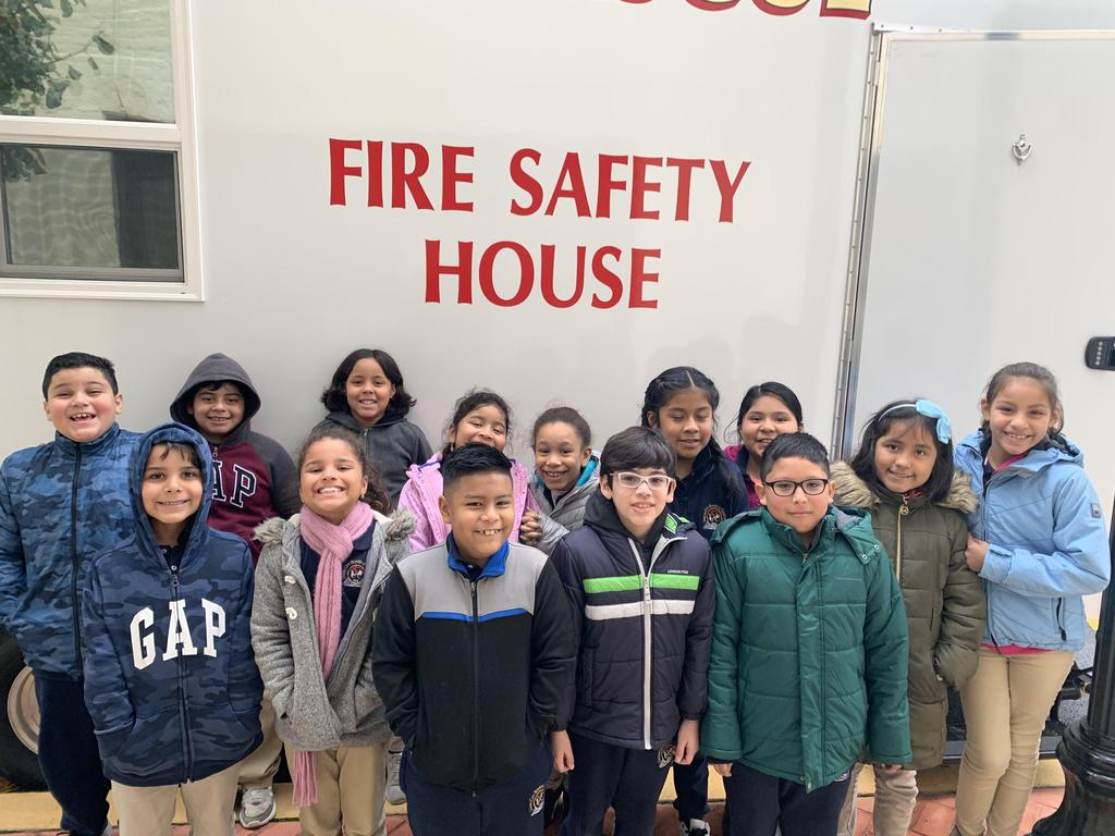 group of children standing in front of the side of the fire safety house