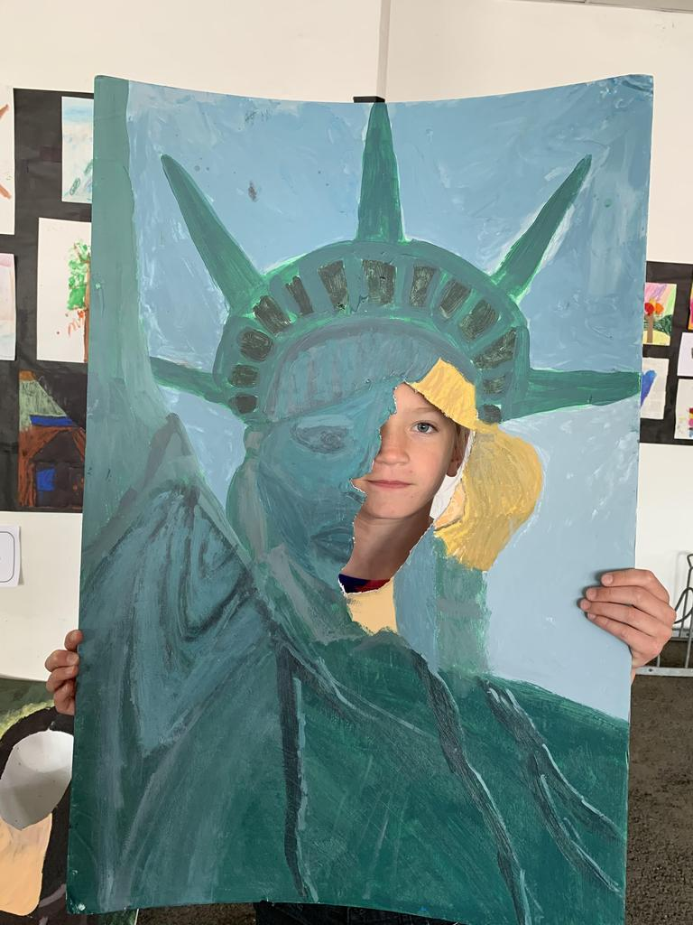 child posing in statue of liberty painting