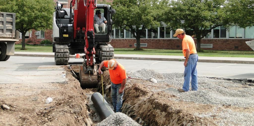 Site construction workers install a drainage pipe.