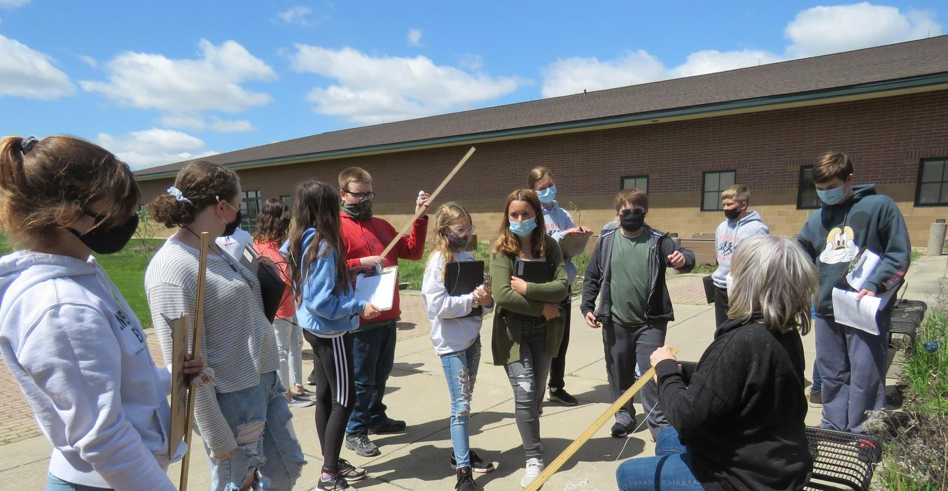 TKMS science teacher Jamie Bowman talks with her class outside about their assignment.