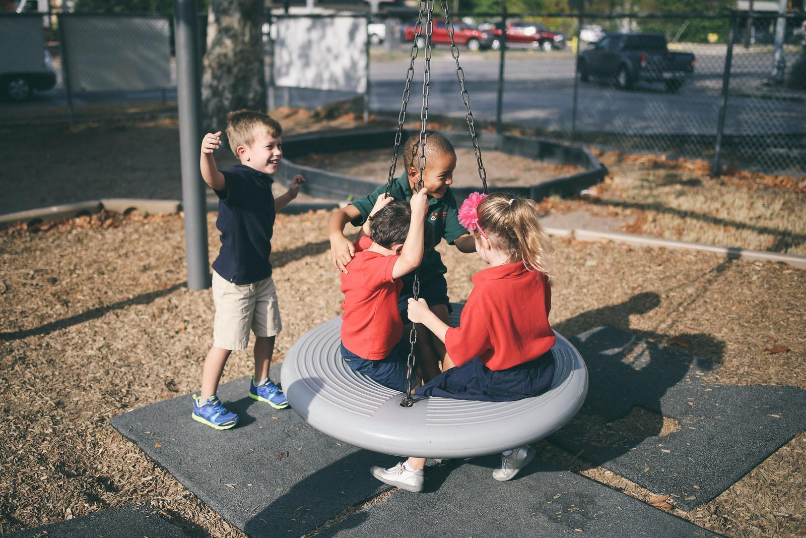 students playing on tire swing