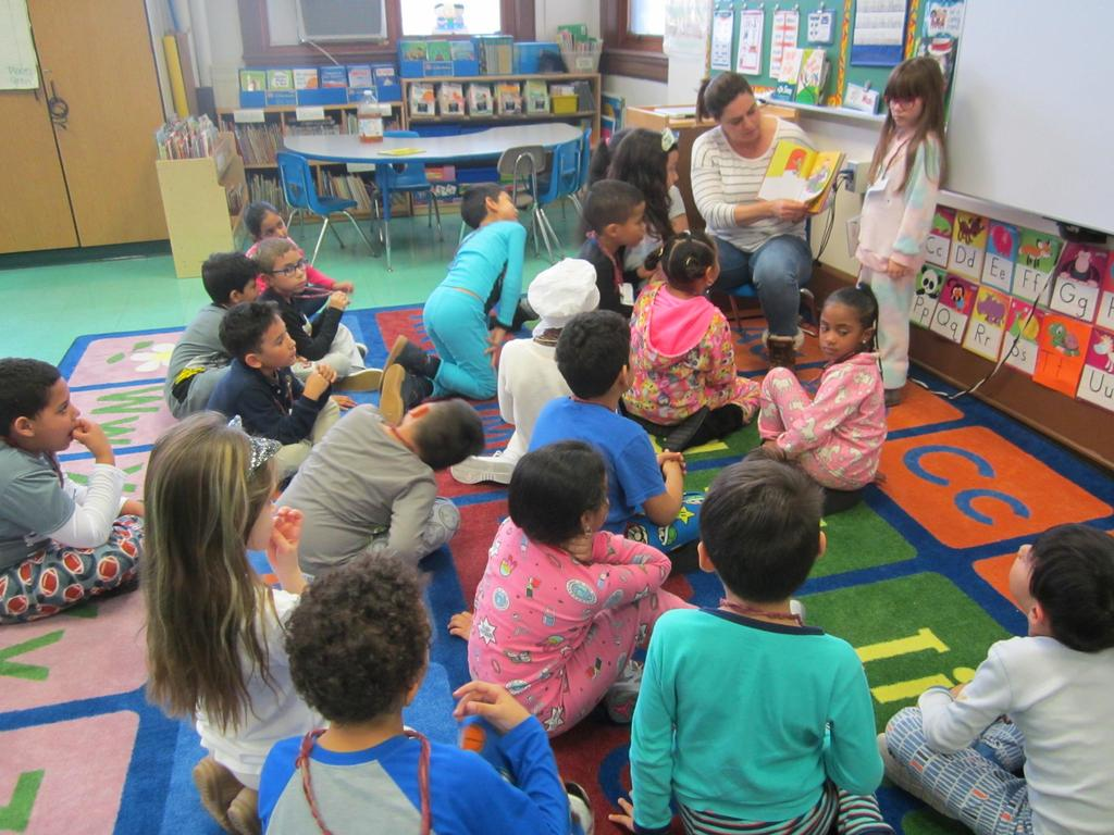 mom reading to a group of children dressed in pj's on the class rug