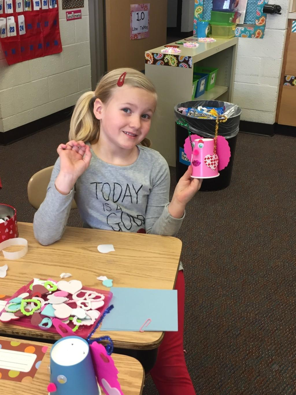 girl holds up her Valentine craft made from paper cup