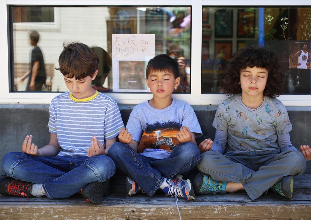 Image of three boys, a boy with short brown hair wearing a blue and white striped shirt, a boy wit short dark brown hair wearing a t-shirt with a robot on it, and a boy with medium length curly dark hair wearing a grey shirt. The boys sit in front of a window in lotus position with their eye closed and their hands upturned on their knees.