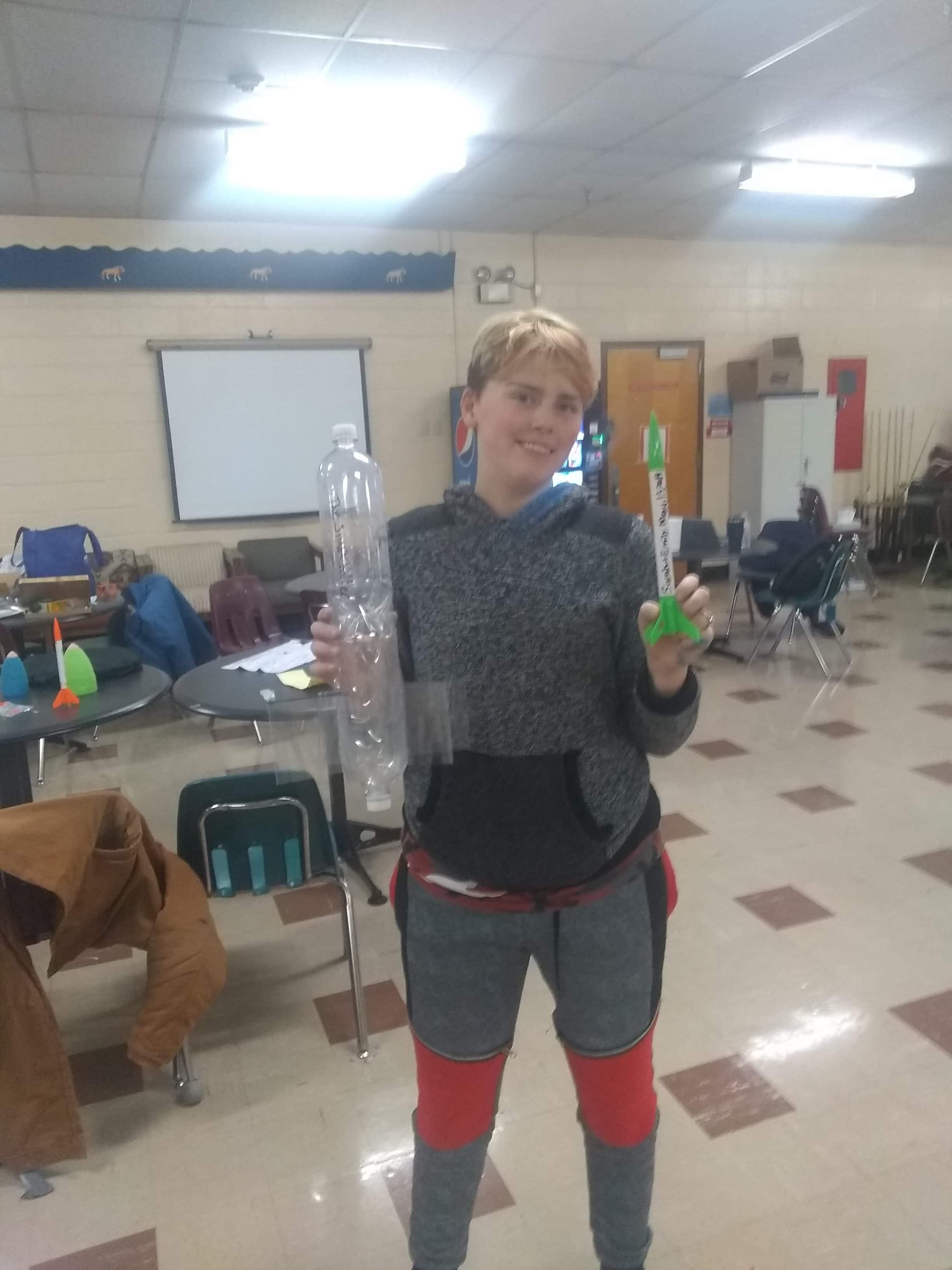 Female student in gray sweatshirt holds two liter bottles in right hand and small rocket in left hand