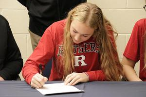 Close up of Regan signing her papers