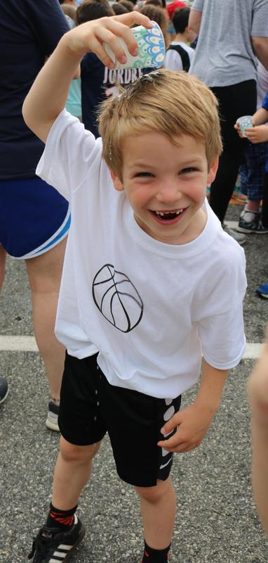 Wilson School student smiles widely as he pours water on his head to cool off during Field Day.