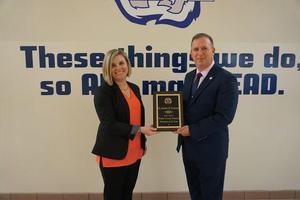 Dr. Heather Melton receives award from Superintendent Mark Byrd.