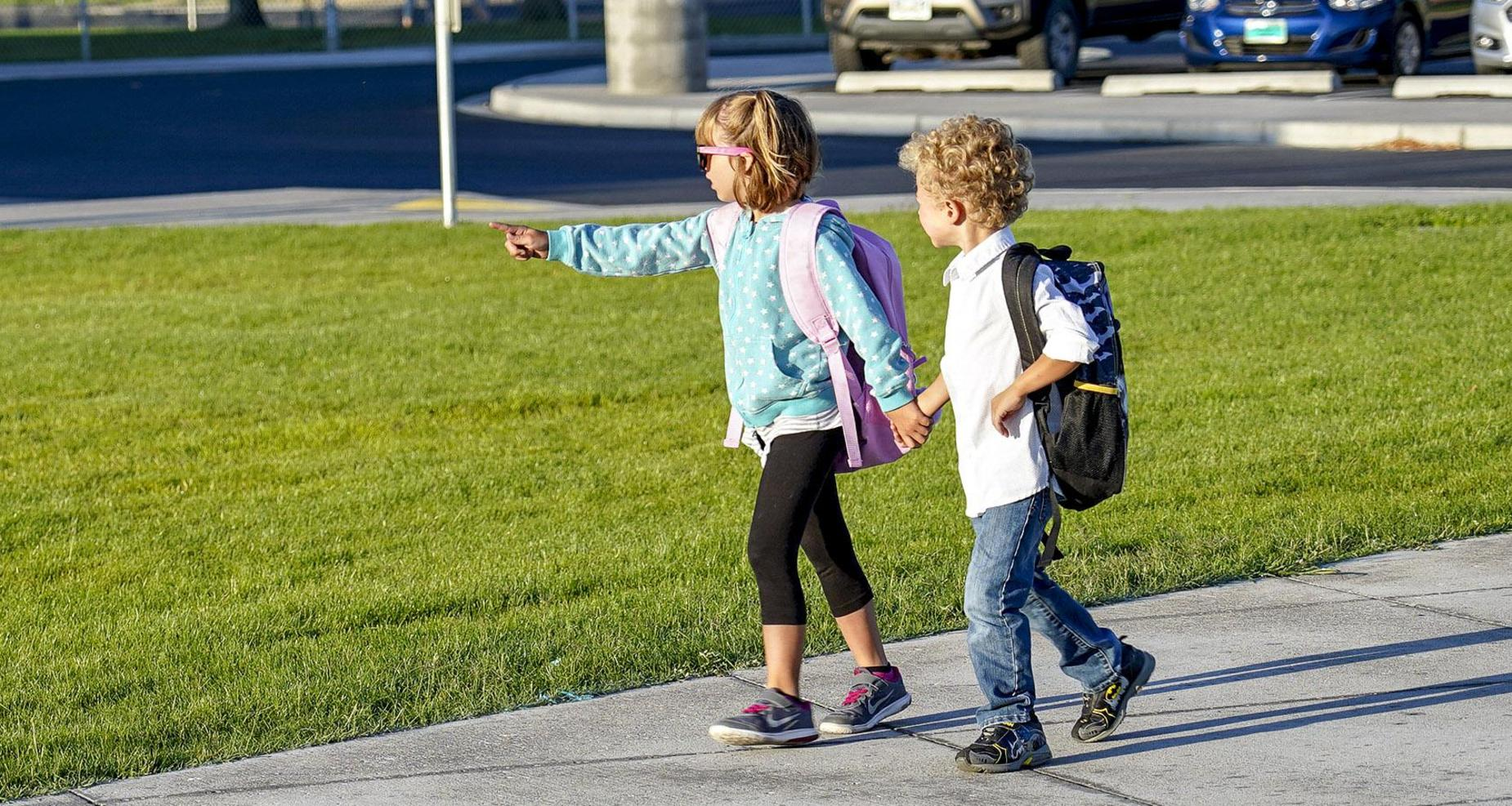 Siblings walking to school together holding hands.