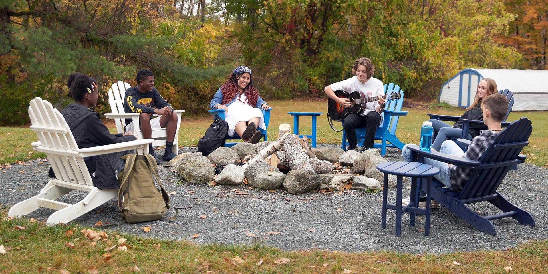 A group of students around a firepit listening to a student on the guitar.