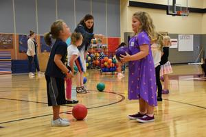 Two kindergarten students playing toss in the gym.