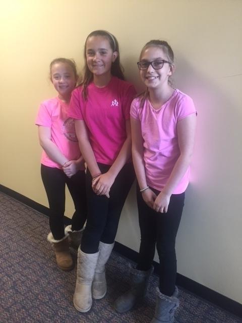 three girls in pink shirts smile