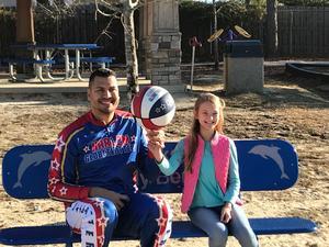 "Sarah-Katherine Cantrell visits with Orlando ""El Gato"" Melendez, a member of the Harlem Globetrotters basketball team."