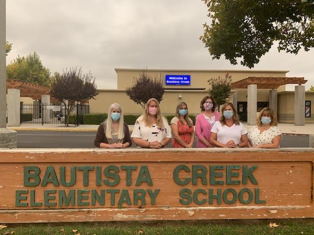 Terri, Lori, Lorraine, Ruby, Christi, and Melissa in masks standing in front of the Bautista Creek Elementary sign.
