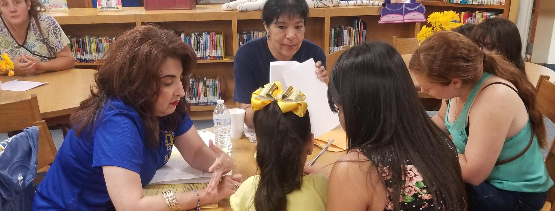 Teachers help parents register children for school