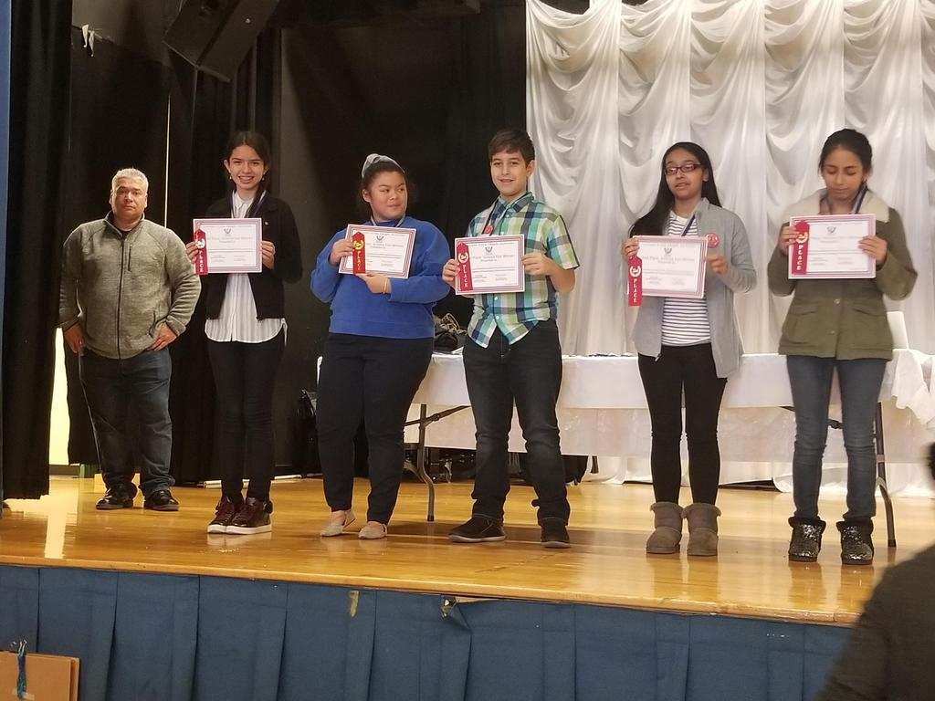 uhms students on stage with their certificates with mr. sanchez