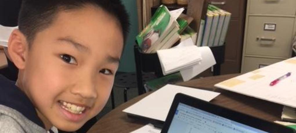 A student smiles with his chromebook.