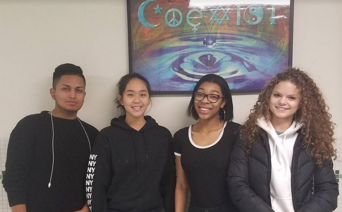 4 students stand under a coexist poster