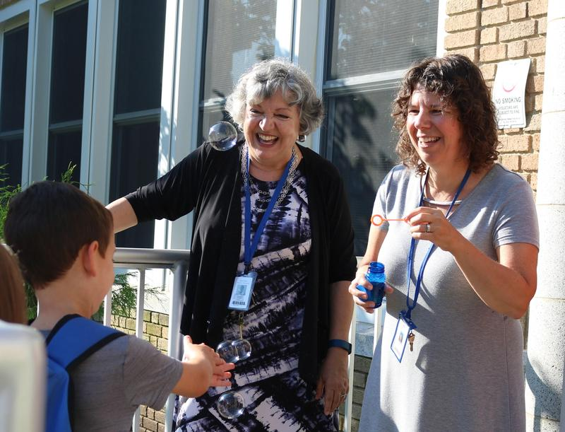Lincoln School teacher blows bubbles to the delight of a student, as principal Audrey Zavetz looks on.