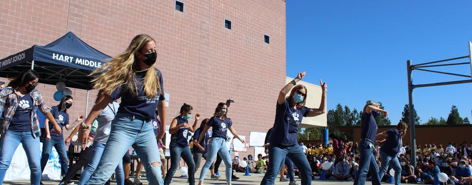 Giving the crowd a reason to cheer, teachers present at line dance assembly.