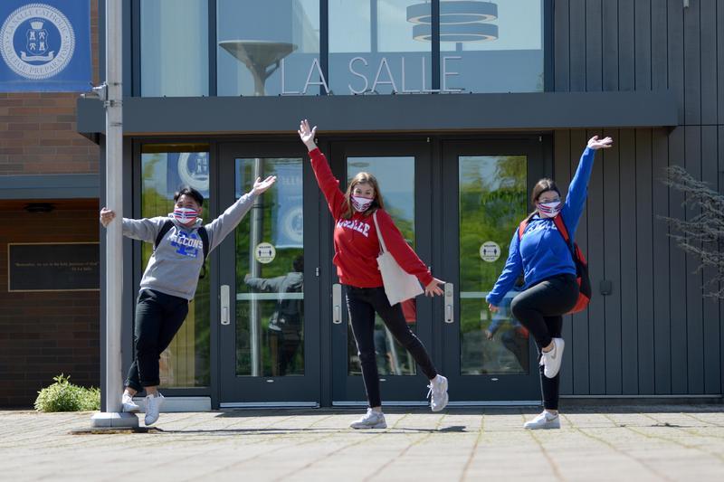 three students standing in front of door of la salle school