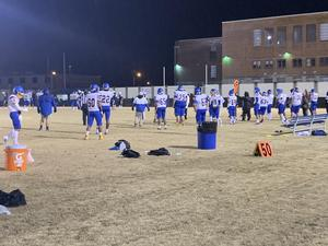 The image is of the varsity football team in their white and blue uniforms. They stand on the sideline of the field. There is an orange gatorade cooler on the ground.