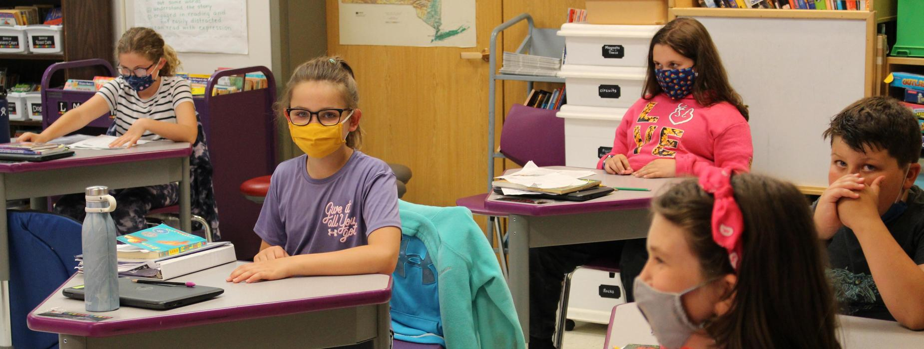 Students working at their desks with masks on