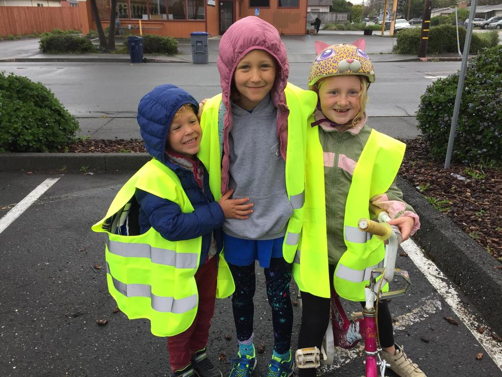 3 students posing in reflective safety vests