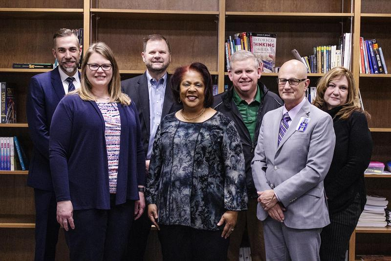 7 administrators pose together in front of a bookcase