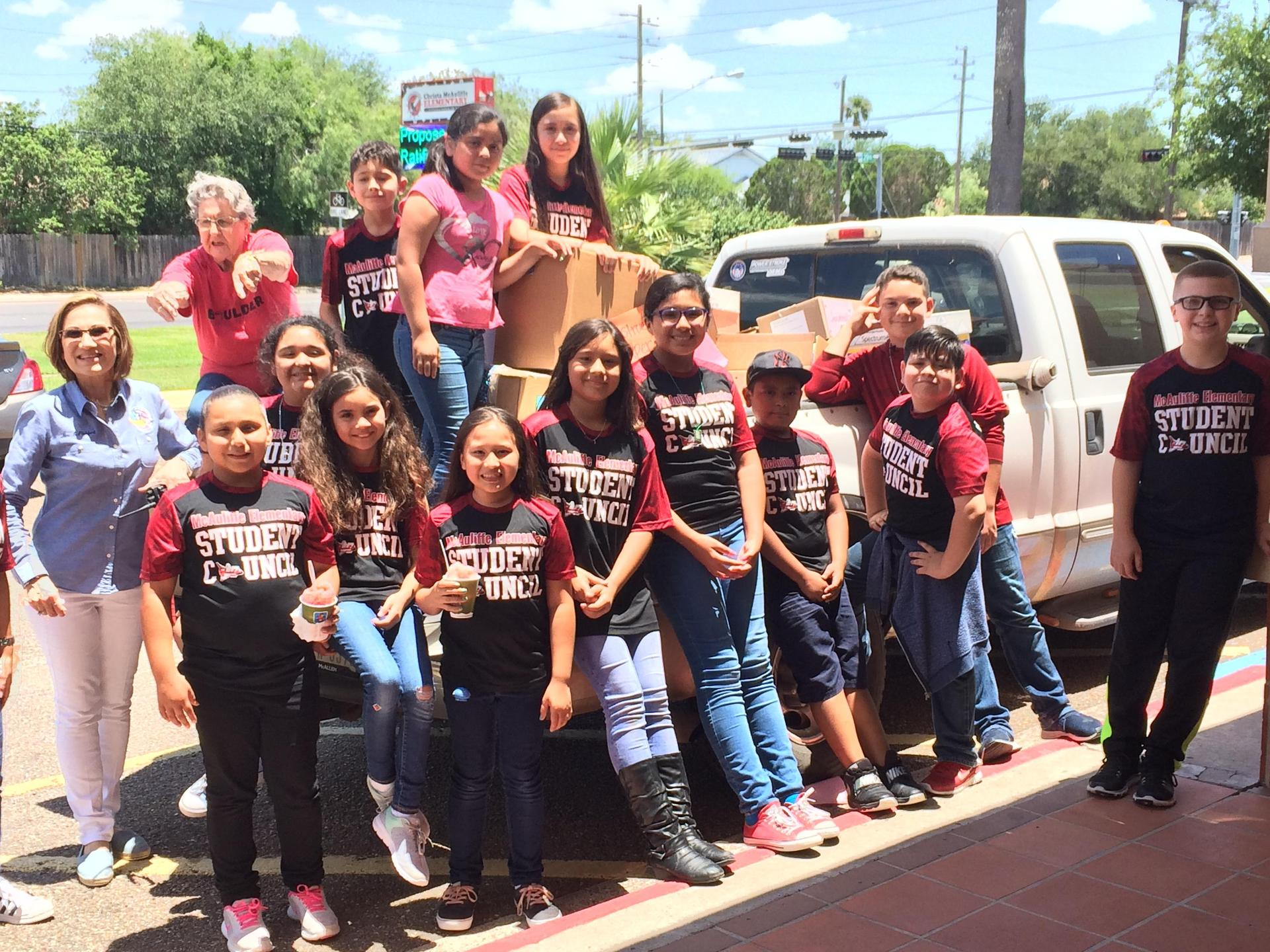 Students posing with truck full of donated supplies.