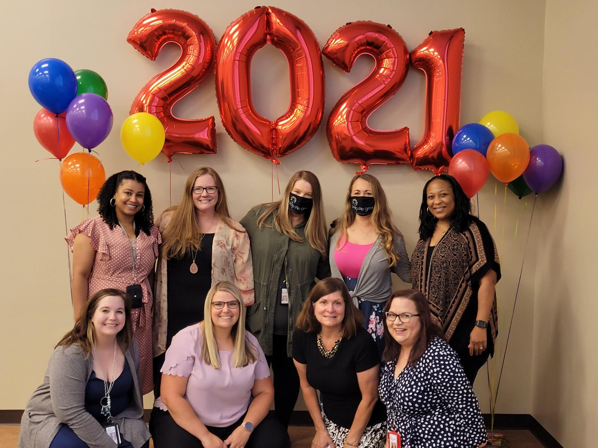 Help Me Grow and Every Child Succeeds staff standing in front of 2021 balloon graduation banner