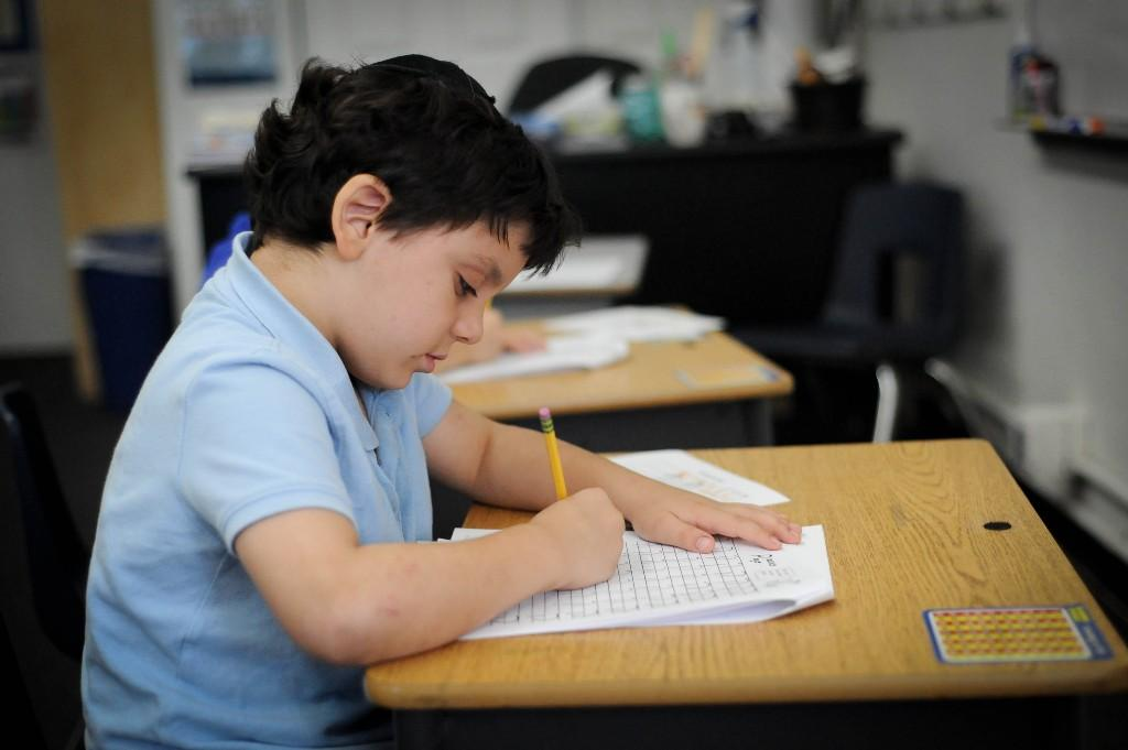 Boy filling out a worksheet in class
