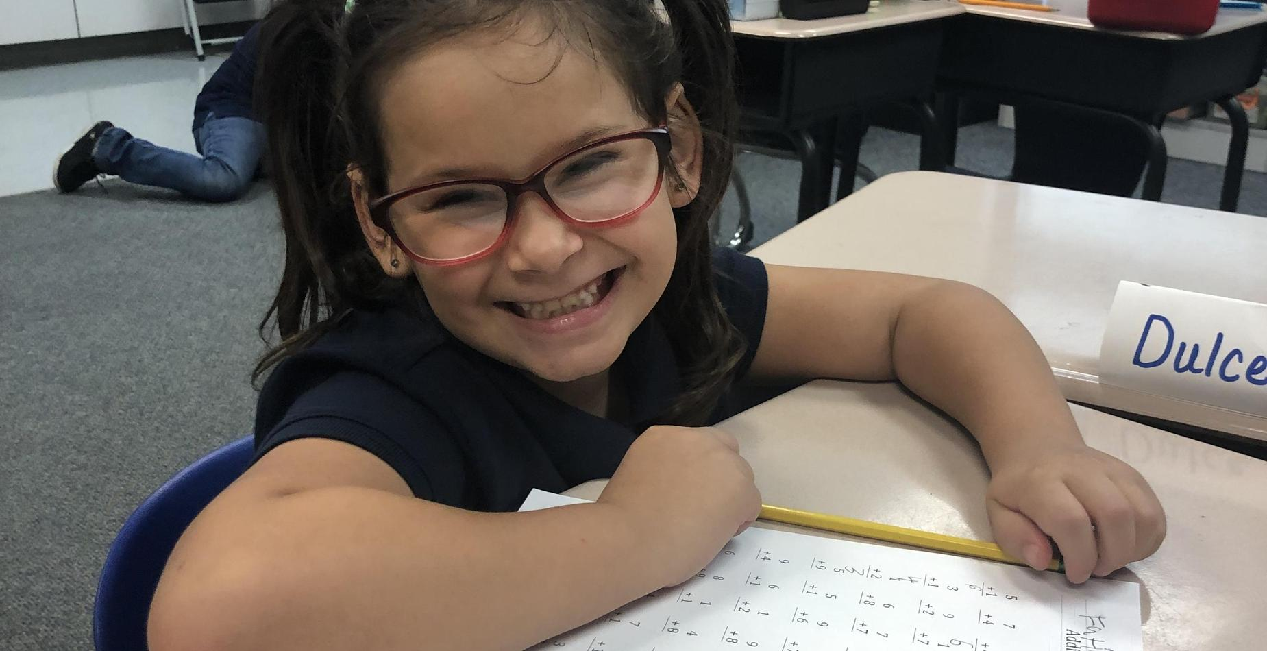 a second grade girl smiling as she completes her math assignment
