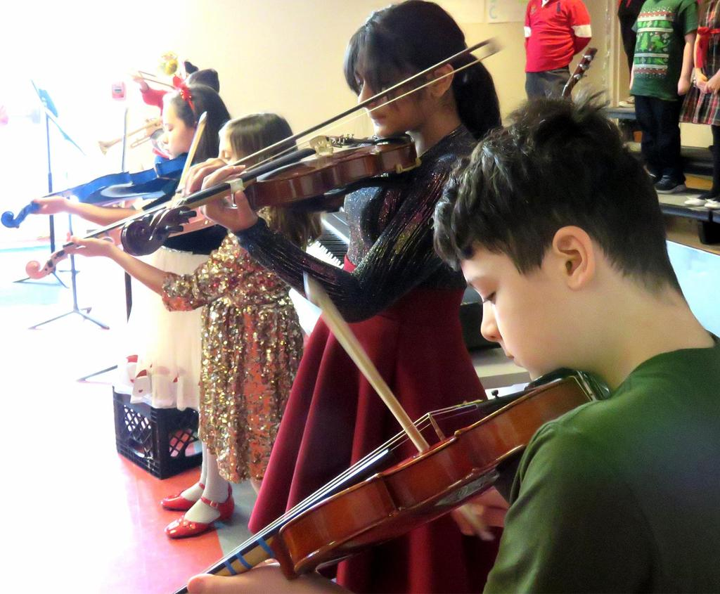 A sideway view of four violin players