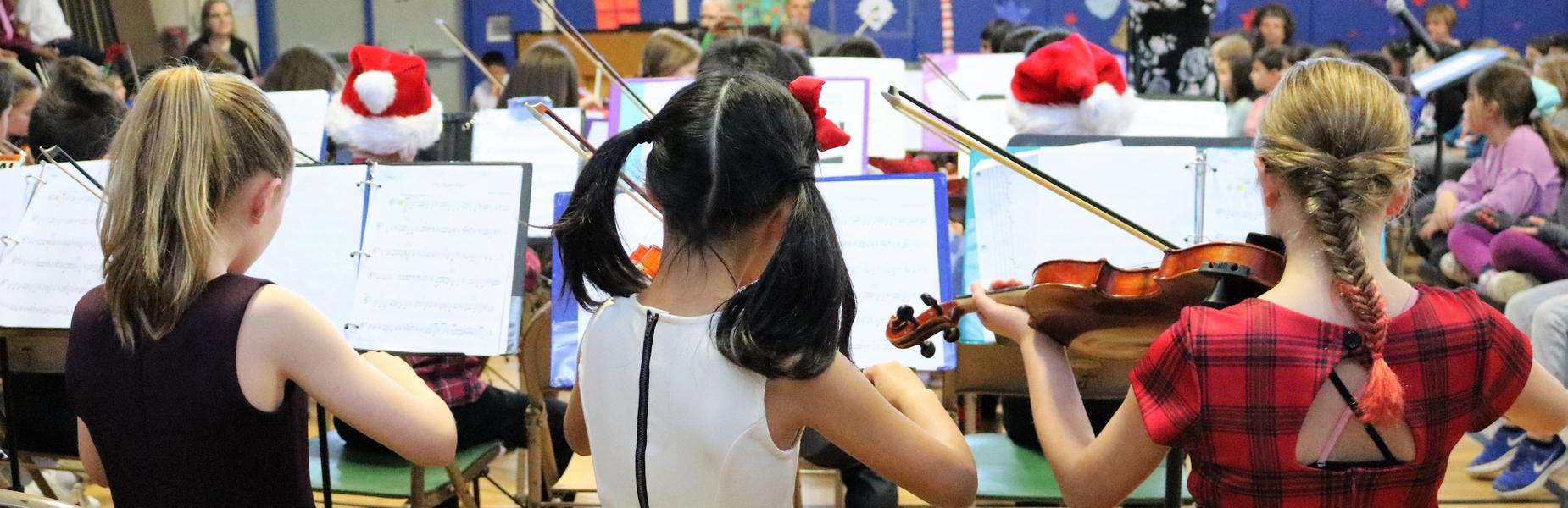 Photo of backs of three Grade 5 violinists during winter concert at Jefferson School.