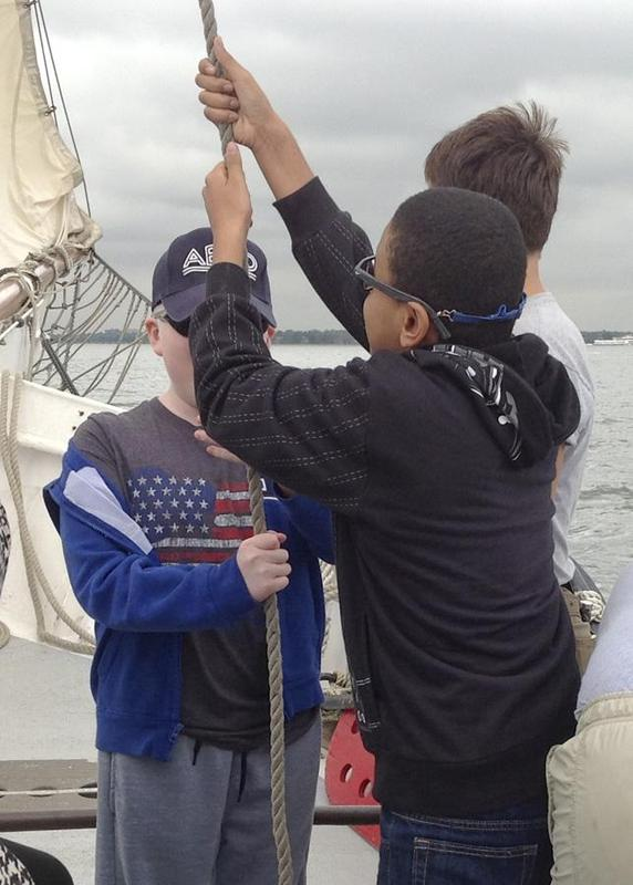 Student pulling a rope to help raise the sails.