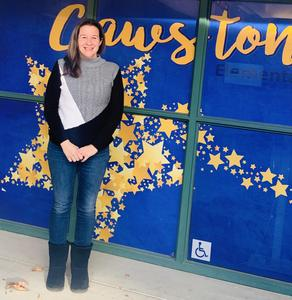 Jennifer Hockman in front of a Cawston Elementary sign.