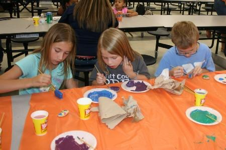 These students are working hard painting their rocks.