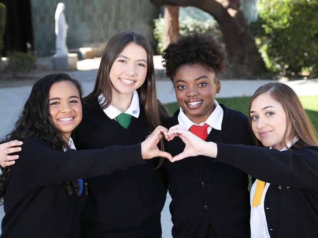 four students posing with two students making the shape of a heart with their hands
