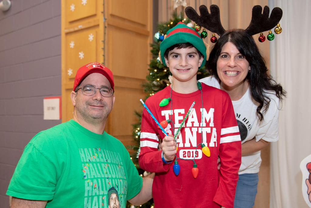 """A student wearing a """"Team Santa"""" shirt is flanked by his mother and father"""