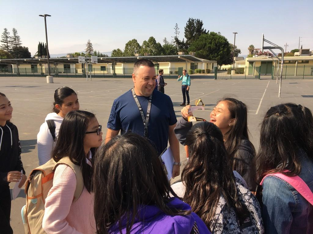Students with teacher laughing and trying on solar eclipse glasses