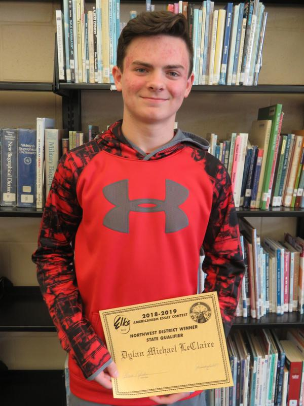 Dylan LeClaire receives an award for his essay.